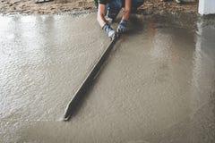 Muratore che costruisce un cemento del cappotto di tirata immagine stock libera da diritti
