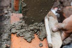 Muratore che costruisce una casa facendo uso degli strumenti e del cemento Immagini Stock