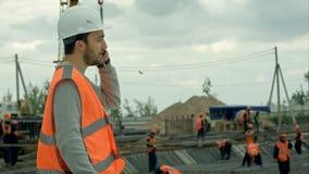 Muratore che parla sul telefono ad un cantiere video d archivio