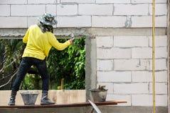Muratore che per mezzo della cazzuola per intonacare il calcestruzzo per costruire parete, Co Fotografia Stock Libera da Diritti