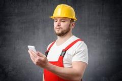 Muratore che per mezzo dello smartphone immagine stock libera da diritti
