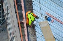 Muratore che rende a rinforzo sito in costruzione Immagine Stock