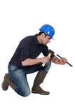 Muratore con il martello e lo scalpello fotografia stock