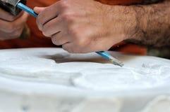 Muratore di pietra sul lavoro che scolpisce un sollievo ornamentale Immagine Stock