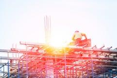 Muratore durante il lavoro di rinforzo con i coni retinici del tondo per cemento armato del metallo al cantiere Fotografia Stock Libera da Diritti