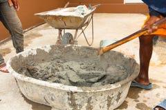 Muratore durante per mezzo della zappa per mescolare cemento bagnato Fotografia Stock