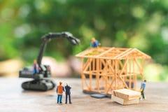 Muratore miniatura della gente riparare un modello di modello della casa usando come il concetto del bene immobile del fondo e co fotografie stock libere da diritti