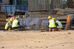 Muratori che fabbricano la barra di rinforzo del cappuccio di mucchio al cantiere Immagini Stock Libere da Diritti
