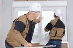 Muratori che installano finestra nella casa fotografie stock libere da diritti