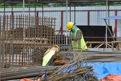 Muratori che lavorano ai lavoratori di piegamento di yardConstruction della barra d'acciaio che lavorano all'iarda di piegamento  Immagine Stock