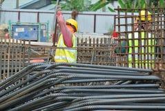 Muratori che lavorano ai lavoratori di piegamento di yardConstruction della barra d'acciaio che lavorano all'iarda di piegamento  Immagini Stock Libere da Diritti