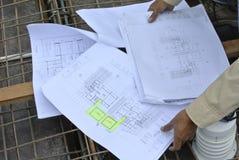 Muratori che si riferiscono al disegno di costruzione Fotografia Stock Libera da Diritti