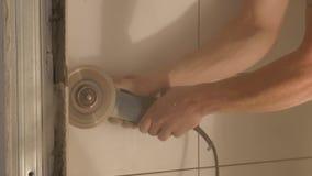 Muratori che usando smerigliatrice per sistemare i bordi delle mattonelle al cantiere Il lavoratore passa il taglio della piastre video d archivio