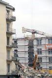 Muratori durante la demolizione di una casa con una gru Immagine Stock