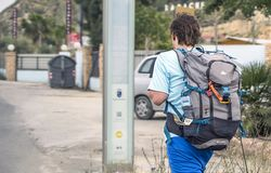 Murcia, Hiszpania, Kwiecień 17, 2019: Młody człowiek jest ubranym ogromnego plecaka odprowadzenie wzdłuż ulicy Podróżować obraz royalty free