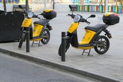 Murcia, Spain - August 4 2018: Environmentally friendly electric. Scooters or mopeds, parked on the pavement, providing a green transport option royalty free stock photography