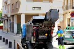 Murcia, Spain - August 4 2018: Waste management operative emptying a domestic rubbish or garbage bin into a small refuse truck be stock photos