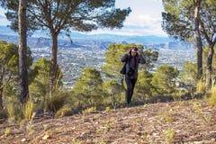 Murcia Spanien - April 9, 2019: gladlynt ung kvinna som fotvandrar och tar bilder med hennes reflex royaltyfri bild