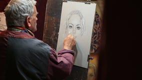MURCIA, 5,2016 SPANJE-MAART: De kunstenaar schildert een portret van een vrouw in een middeleeuwse markt op 5,2016 Maart in Murci stock video