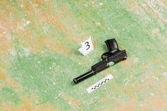 Murder gun lying on the floor. crime scene Royalty Free Stock Images