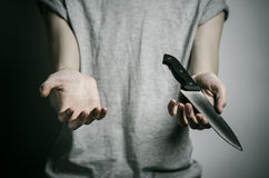 Murder and Halloween theme: a man holding a knife on a gray background Royalty Free Stock Photo