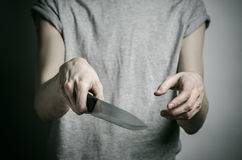 Murder and Halloween theme: a man holding a knife on a gray background Royalty Free Stock Photography