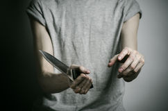 Murder and Halloween theme: a man holding a knife on a gray background Stock Images