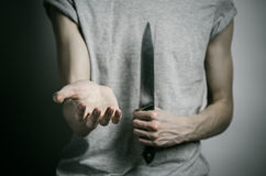Murder and Halloween theme: a man holding a knife on a gray background Stock Photos