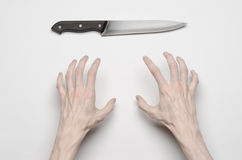 Murder and Halloween theme: A man's hand reaching for a knife, a human hand holding a knife isolated on a gray background in studi Stock Images