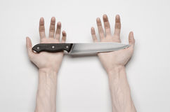 Murder and Halloween theme: A man's hand reaching for a knife, a human hand holding a knife isolated on a gray background in studi Royalty Free Stock Images