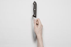 Murder and Halloween theme: A man's hand reaching for a knife, a human hand holding a knife isolated on a gray background in studi Stock Photo