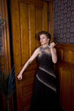Murder Mystery! 2. Beautiful young brunette woman holding a knife about to open a door Stock Image