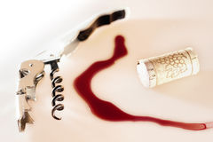 Murder, It's corked. A wake of blood-like poured red wine stuck between a cork and a Laguiole bar knife royalty free stock images