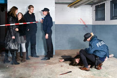 Murder Scene. Bystanders being held at a distance by a police man at a murder scene, with a police woman tending to the victim Royalty Free Stock Photo