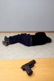 Murder or suicide. Dead man lying on the floor and a pistol standing on the table.Murder or suicide Royalty Free Stock Photos