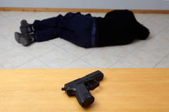 Murder or suicide. Dead man lying on the floor and a pistol standing on the table.Murder or suicide Stock Photos