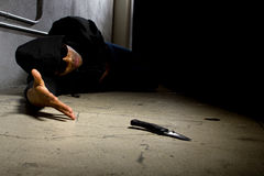 Murder Victim By Gang Violence. Man in a street alley killed with a knife and victim of gang violence Stock Photography