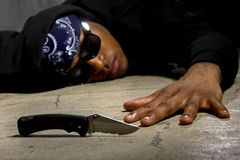 Murder Victim By Gang Violence. Man in a street alley killed with a knife and victim of gang violence Royalty Free Stock Photography