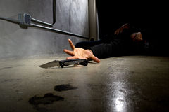 Murder Victim By Gang Violence. Man in a street alley killed with a knife and victim of gang violence Stock Photo