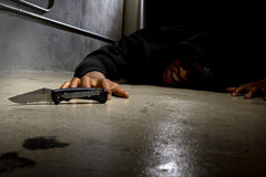 Murder Victim By Gang Violence. Man in a street alley killed with a knife and victim of gang violence Royalty Free Stock Photo