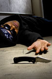 Murder Victim By Gang Violence. Man in a street alley killed with a knife and victim of gang violence Royalty Free Stock Image