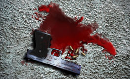 The murder weapon. An automatic gun and several cartridges on a  pool of blood on the ground Stock Photography