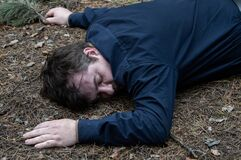 Murder in the woods. The body of a man in a blue shirt lies on the ground among the trees in the forest. Victim of an attack