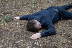 Murder in the woods. The body of a man in a blue shirt and trousers lies on the ground among the trees in the forest. Victim of an