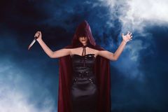 Murderer asian witch woman with red cloak holding bloody knife Stock Photos