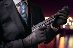 Murderer or killer holds pistol with silencer in hands at night.  stock photo