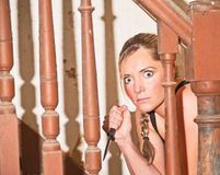Murderous woman with dagger. Attractive young woman with frightened expression  creeping up a stair holding a dagger Royalty Free Stock Images