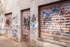 Muren en sluizen door slechte graffiti worden gesmeerd die Vandalenstreek Royalty-vrije Stock Foto's
