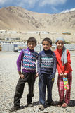 MURGHAB, TAJIKISTAN - JULY 18 2016 Young children of Murghab. MURGHAB, TAJIKISTAN - JULY 18 2016 Young children, two boys and girl posing in the town center of Royalty Free Stock Photography