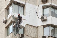 Muri l'isolamento termico, la scalata industriale, il lavoro ad alta altitudine, l'isolamento delle pareti con la plastica della  Fotografie Stock